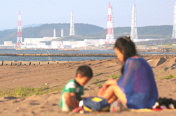 A woman and child sit on a beach as Tokyo Electric Power Co.'s (Tepco) Kashiwazaki Kariwa nuclear power station stands in the background in Kashiwazaki City, Niigata Prefecture, Japan, on Friday, Sept. 6, 2013. Niigata Governor Hirohiko Izumida痴 approval is critical before Tepco can go ahead with plans for the restart of Kashiwazaki-Kariwa, the world痴 largest nuclear power station by generating capacity. Photographer: Yuriko Nakao/Bloomberg