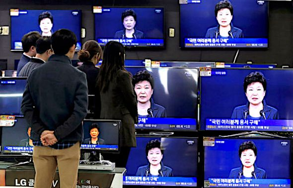 in the Nov. 4, 2016 photo, people watch TV screens showing the live broadcast of South Korean President Park Geun-hye's addressing to the nation at the Yongsan Electronic store in Seoul, South Korea. (AP Photo/Ahn Young-joon)