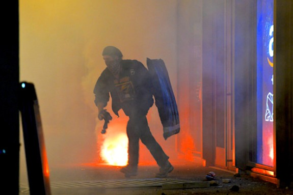 A protester runs back after smashing windows during a protest against right-wing troll Milo Yiannopoulos who was scheduled to speak at UC Berkeley on Wednesday, Feb. 1, 2017. (Doig Duran/Bay Area News Group)