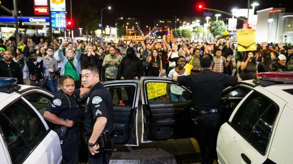 Protesters stare down Los Angeles police officers during a November 2014 demonstration against a Missouri grand jury's decision not to indict the officer who fatally shot Michael Brown. Protests erupted across the country after the announcement. (Marcus Yam / Los Angeles Times)