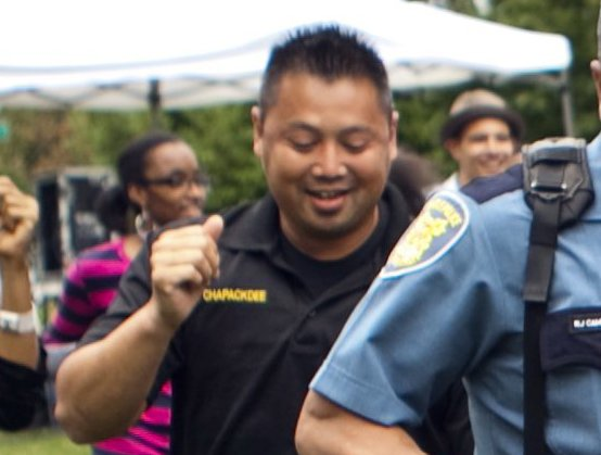 From left, Seattle Police Officers Alex Chapackdee, Jojo Cambronero, James Manning and Craig McRae do the Cupid Shuffle with the crowd at the Othello Park International Music and Arts Festival at Othello playground in South Seattle Sunday, August 19, 2012.
