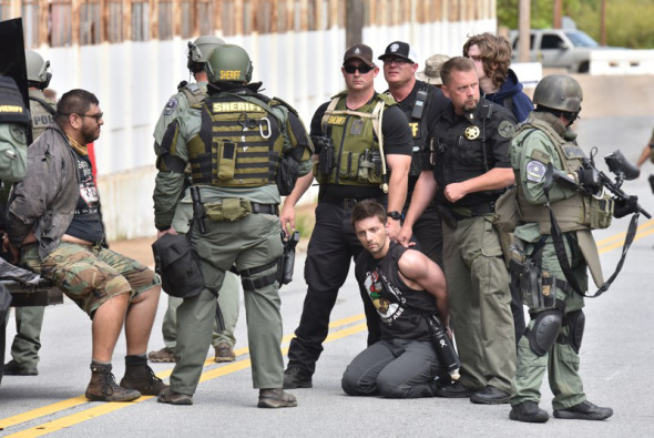 Counterprotesters are held by law enforcement officers as the National Socialist Movement holds a rally at Greenville Street Park in downtown Newnan on Saturday, April 21, 2018. The far-right hate group also drew anti-fascist demonstrators as well as hundreds of police officers. (HYOSUB SHIN / AJC)