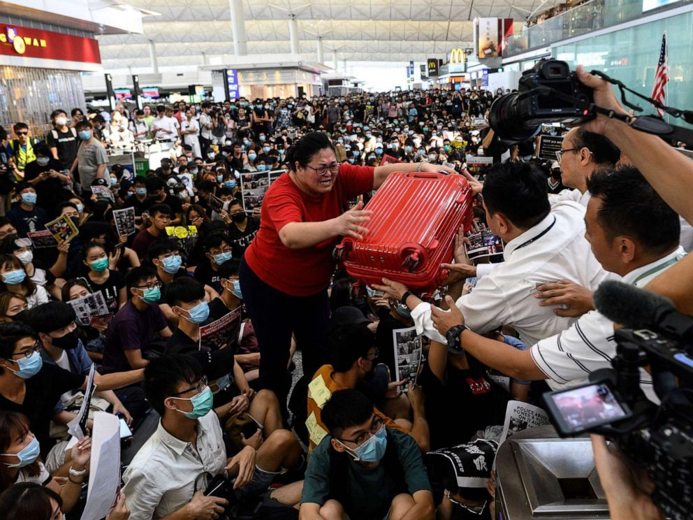 PHOTO: A tourist gives her luggage to security guards as she tries to enter the departures gate during another demonstration by protesters at Hong Kongs International Airport on Aug. 13, 2019.